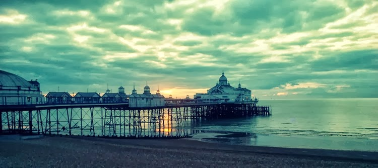 sun peaking behind the pier