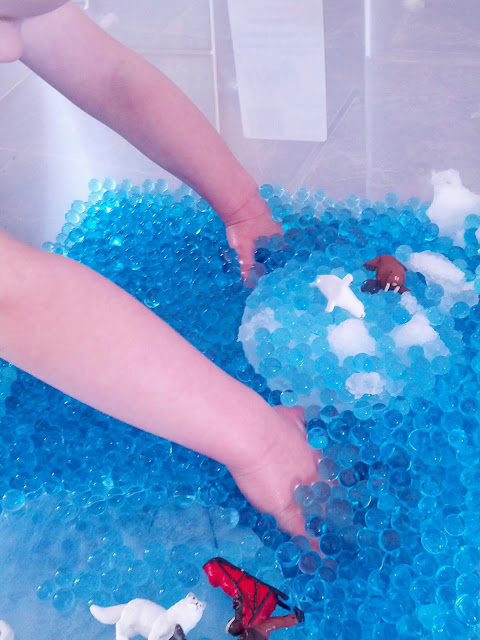 Blue water beads in an arctic sensory bin