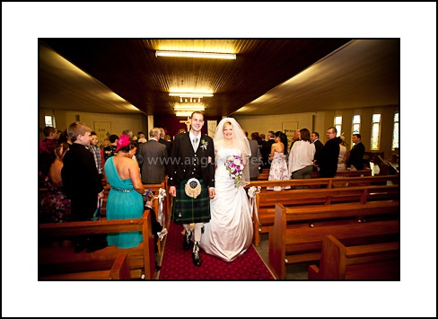 Bride and groom exit church after service