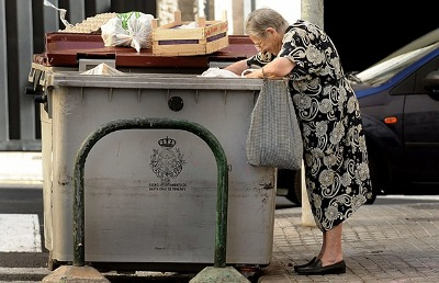 old woman looking in a dumpster