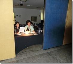 Irene e Verena fazendo a narração do filme Náufrago, com o roteiro em mãos, de frente para os microfones, no fundo da sala de exibição
