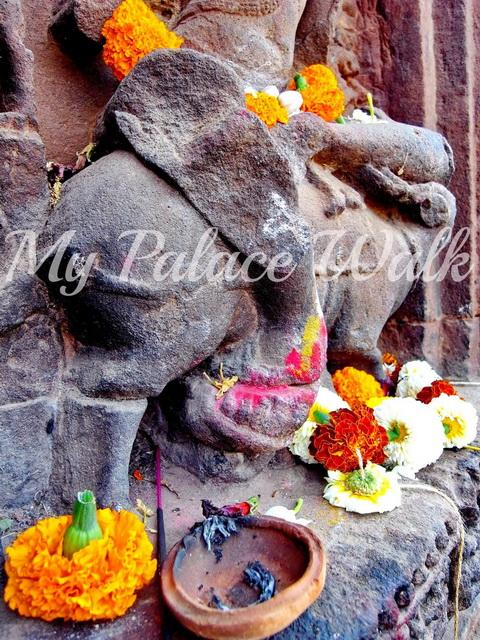 Flowers, incense and other offerings to stone engraving of figure riding sacred cow, India