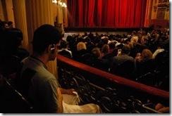 Audiodescrição - pessoas sentadas em uma plateia; pessoa cega em destaque usando fones de ouvido