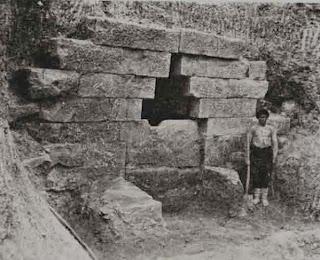 человек стоит рядом с входом в каменную гробницу в Мезеке, болгария