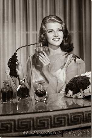 Actress Rita Hayworth with a collection of fragrances