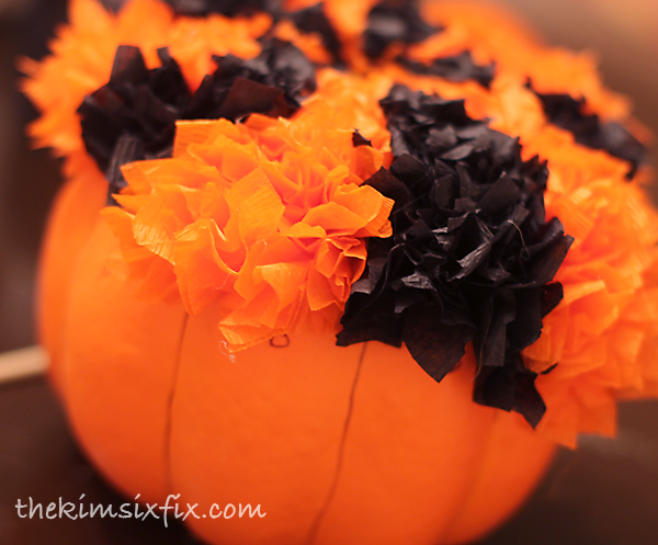 Applying tissue paper to pumpkin