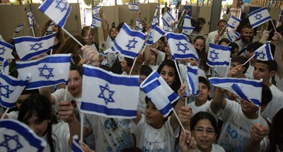 Israeli children wave their national flag as they welcome immigrants to Israel's Ben Gurion airport on May 5, 2008. Four hundred immigrants from 23 countries arrived in Israel today as part of Israel's 60th anniversary celebrations.  AFP PHOTO/DAVID FURST (Photo credit should read DAVID FURST/AFP/Getty Images)