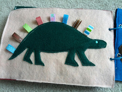 Dinosaur taggy quiet book page from And Next Comes L