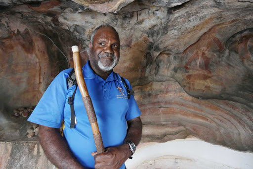 Australia-Queensland-Bama-Way-Cave-Painting-Elder - An aboriginal elder stands in front of a Bama Way cave painting during a G Adventures expedition in Queensland, northeastern Australia.