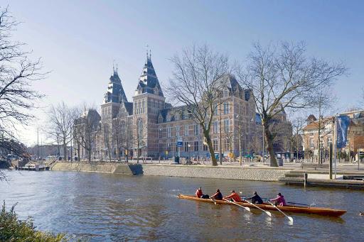 Oarsmen glide past the Rijksmuseum in Amsterdam, Netherlands.