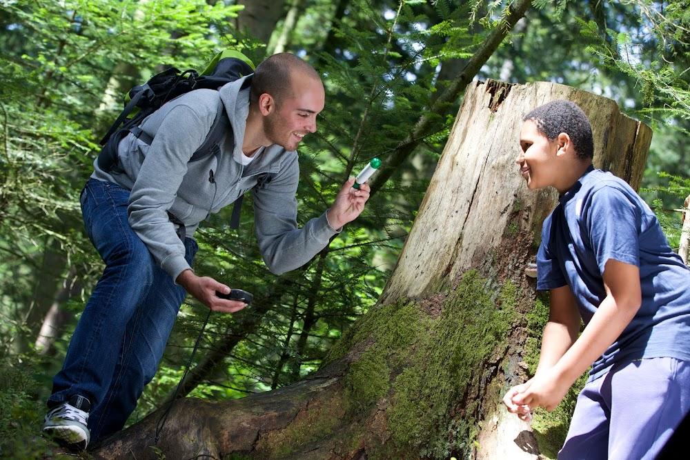 Du siehst zwei junge Männer im Wald mit einem GPS Gerät in der Hand.