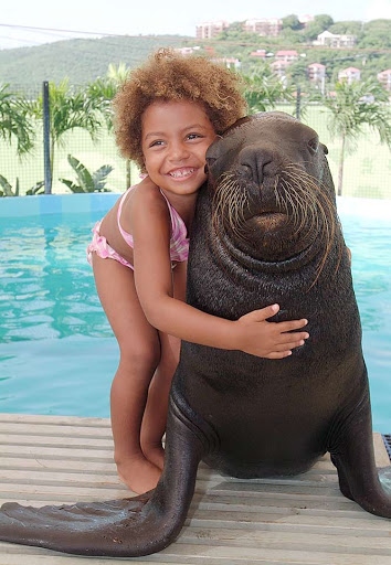 Coral-World-Sea-Lion-Girl - A young girl hugs a sea lion at Coral World Ocean Park in St. Thomas, US Virgin Islands.