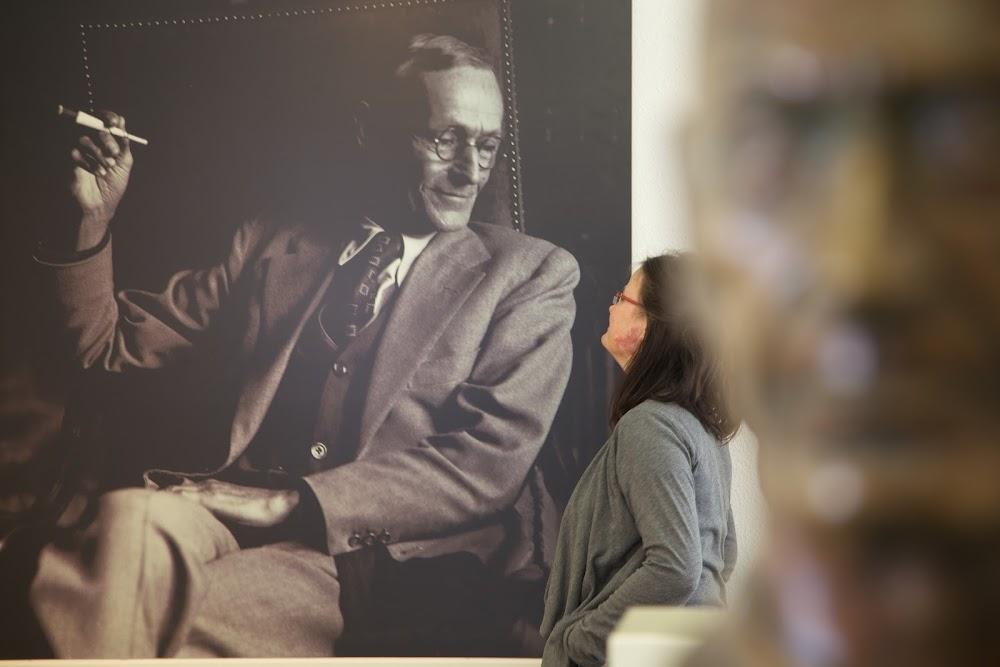 Du siehst eine Frau vor einem Hesse-Bild, im Vordergrund siehst Du eine Skulptur seines Kopfes.