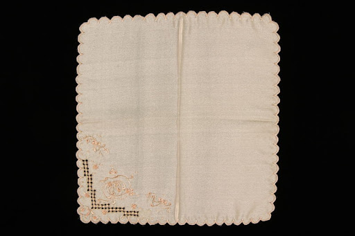 Peach silk handkerchief hand embroidered with ribbons and flowers brought to the US by a Jewish family fleeing German occupied Poland
