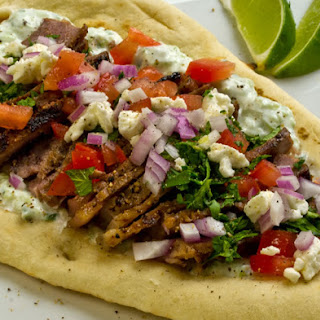 Lime-Marinated Steak Gyros with Tzatziki Sauce, Tomatoes, Onions, Feta, and Mint