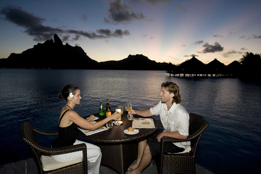 Enjoy a sunset dinner at the St. Regis Bora Bora Resort during your cruise vacation.