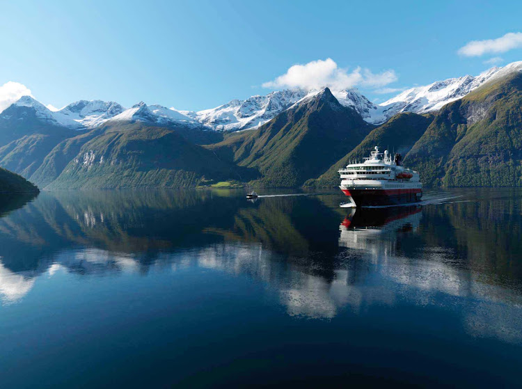 Hurtigruten's Nordnorge sailing during an autumn day along the Hjørundfjorden fjord in Norway where the water has the appearance of glass.