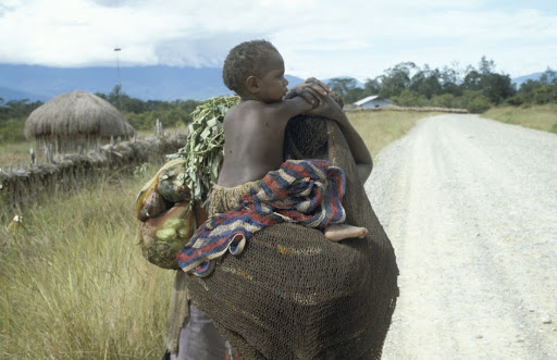 A Dani Papuan woman carrying a child and vegetables in nets on her back