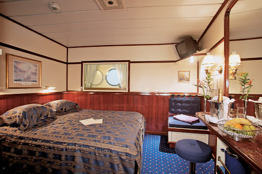 Star-Clippers-Flyer-Owners-Suite-2 - The Owner's Suite aboard Star Clipper and Star Flyer offers   guests a spacious bedroom with a small television, vanity area and king-size bed.