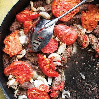 Kefta bil Sayniyeh (Spiced Lamb Patties with Tomato and Onion).