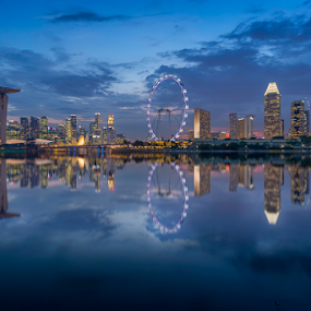 Reflections by the Bay by GokulaGiridaran Mahalingam - City,  Street & Park  Skylines ( canon, clouds, water, flyer, garden by the bay, skyline, suntec, seashore, tall buildings, blue hour, sea, reflections, lake, dusk, 6d, singapore, wide angle, sunset, mbs, buildings, bridge, bridges, pond )