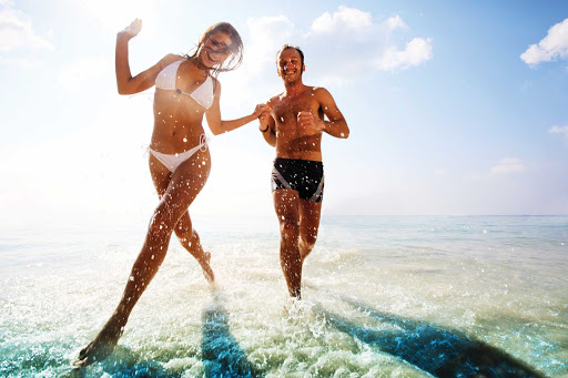 Caribbean-beach-run-couple - Norwegian Cruise Lines offers you passage to a fun, romantic getaway in the Caribbean.