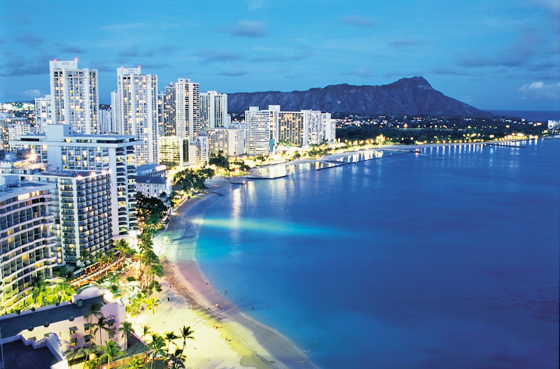 View of world-famous Waikiki Beach with Diamond Head, known locally as Leah, serving as backdrop at dusk.