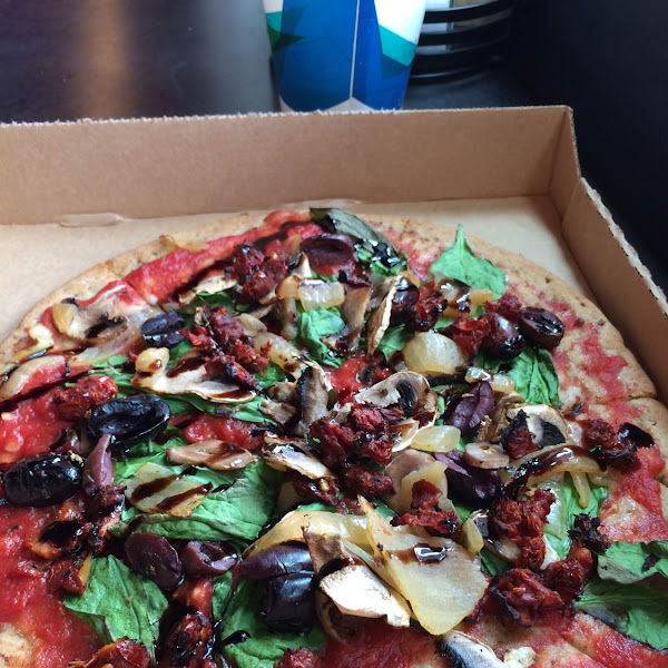 Gluten free, dairy free, vegetarian pizza. Spinach, kalamata olives with onions, mushrooms and sun d