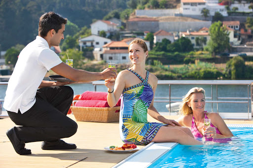 Uniworld-Queen-Isabel-pool-attendant - Guests of Uniworld's Queen Isabel can take adVartage of the attentive service while relaxing poolside during the journey along the endlessly scenic Douro River Valley in Portugal and Spain.