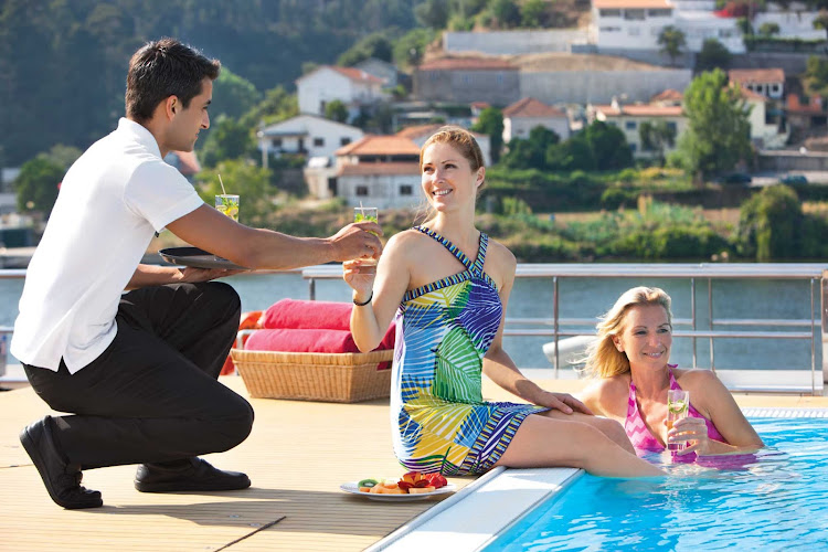 Guests of Uniworld's Queen Isabel can take adVartage of the attentive service while relaxing poolside during the journey along the endlessly scenic DouroRiver Valley in Portugal and Spain.
