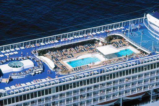 Relax or play hard amid the lounge chairs, pools and nearby bar on Norwegian Sun's pool deck.
