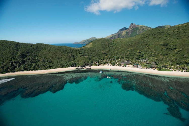 A perfectly still inlet serves as a mirror for Fiji's lush scenery.