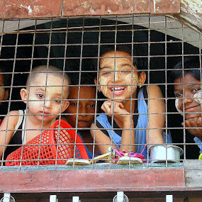 Curious children posing for a pictures by Leong Jeam Wong - Babies & Children Children Candids ( fence, myanmar, yangon burma, caged, rangoon, children, smile, cheerful, sreet, tanaka, kid,  )
