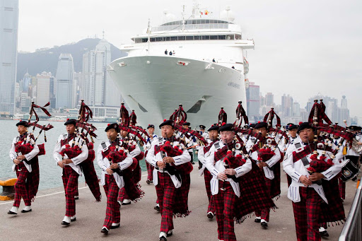 A bagpipe band welcomes a cruise ship to Hong Kong.