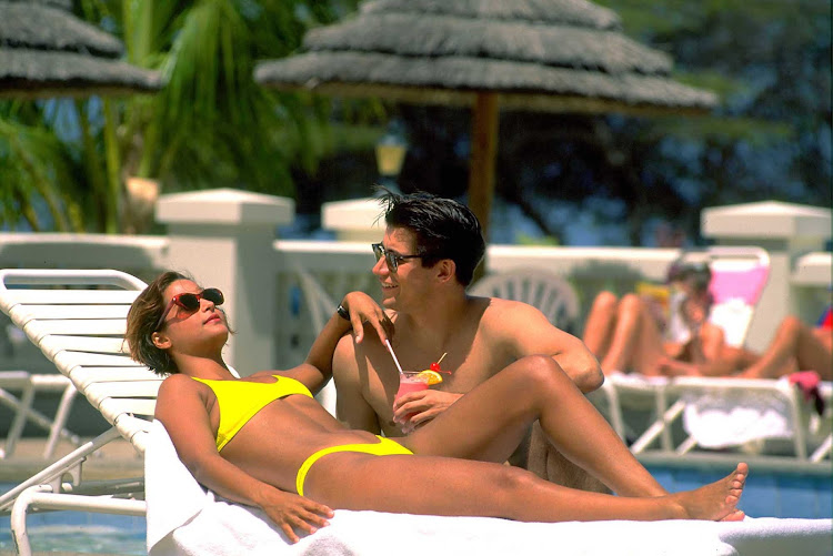 A couple relaxes poolside on Aruba.