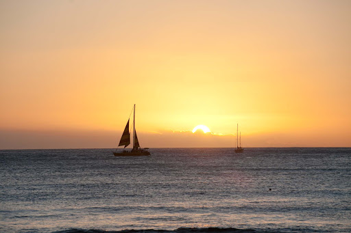 Oahu-sunset - Sailboats skim the Pacific waters off the shore of Waikiki at sunset, as seen from Sans Souci State Recreational Park.