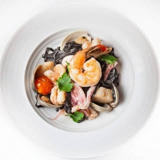Squid Ink Pasta With Seafood, Burst Tomatoes And Sea Urchin Butter.