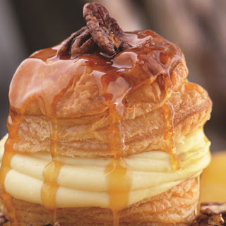 Soufflé of Puff Pastry with Orange-Scented Pastry Cream, Candied Pecans, and Caramel Butter Sauce.
