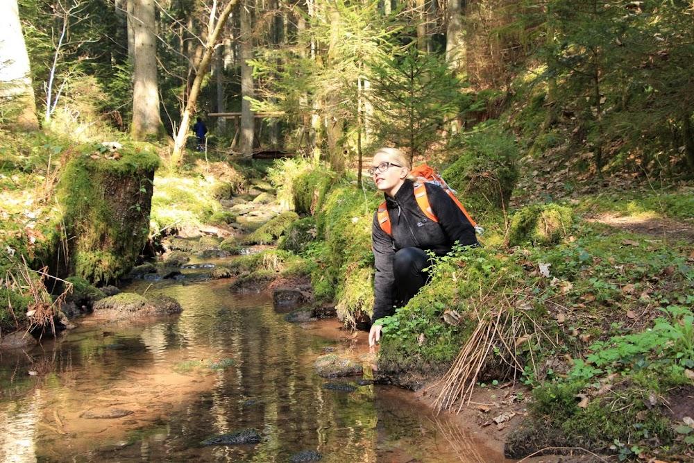 Du siehst eine junge Wanderin am Flussufer sitzen.
