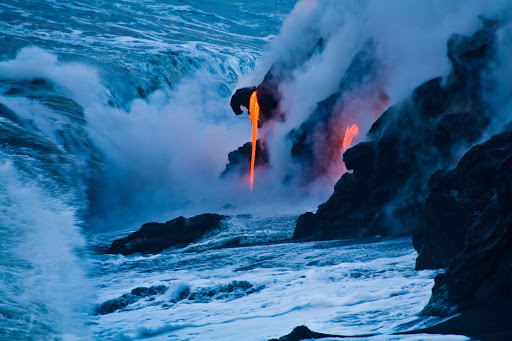 Blue and orange converge as lava enters the sea at dusk at Pahoa on the Big Island of Hawaii.