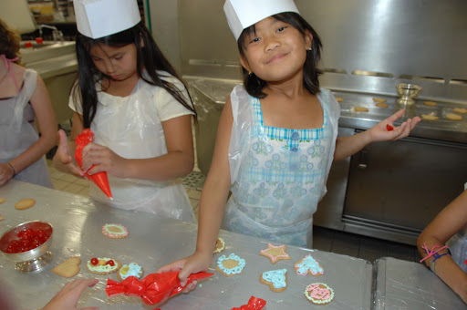 Junior-Cruisers-Kids-Decorating-Cookies-in-the-Galley - Take kids to the Galley to try their hand at pastry decorating, one of the Junior Cruisers activities aboard a Crystal cruise.