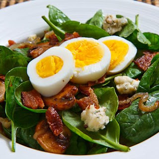 Spinach Salad with Bacon, Caramelized Onions, Mushrooms and Blue Cheese in a Bacon Pan Sauce Dressing Topped with a Hard Boiled Egg.