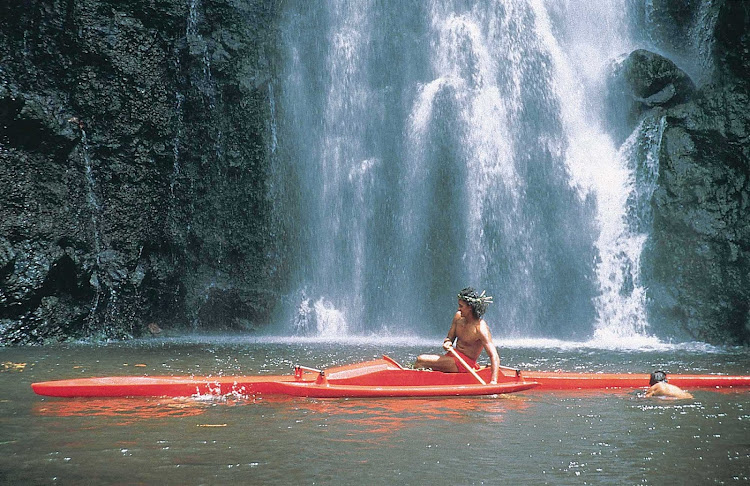 A Tahitian man kayaks near a waterfall on Tahiti. Visitors are encouraged to do the same.