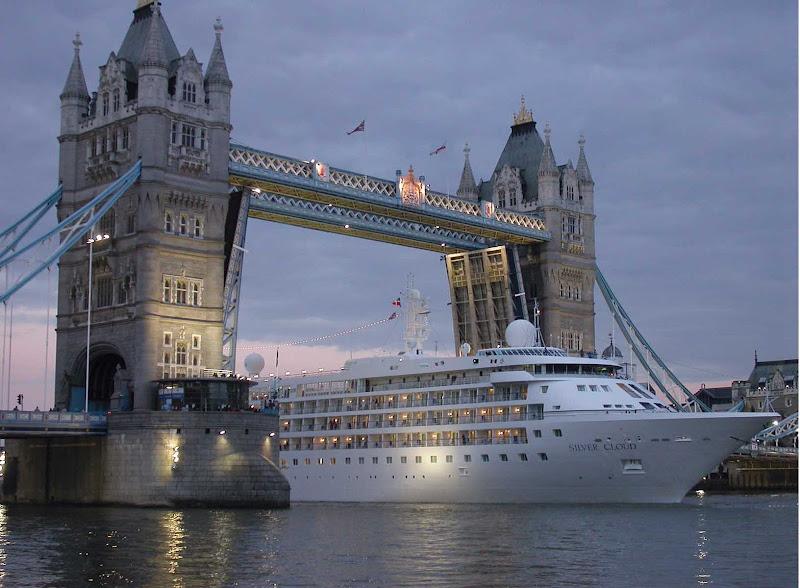 Silver Cloud passes under London's Tower Bridge at dusk.