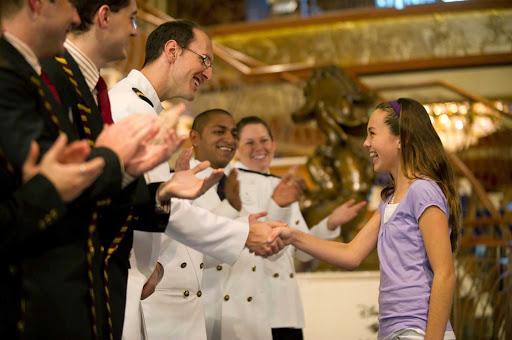 Disney-Dream-Greeting-Young-Guest - Crew members greet a young guest on Disney Dream.