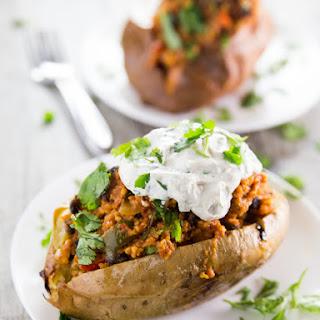 Enchilada Millet Stuffed Sweet Potatoes with Cilantro Garlic Cashew Cream.