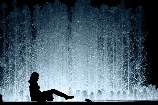 Silhouette of a woman cooling off on a warm spring night in front of the fountain at Lincoln Center.