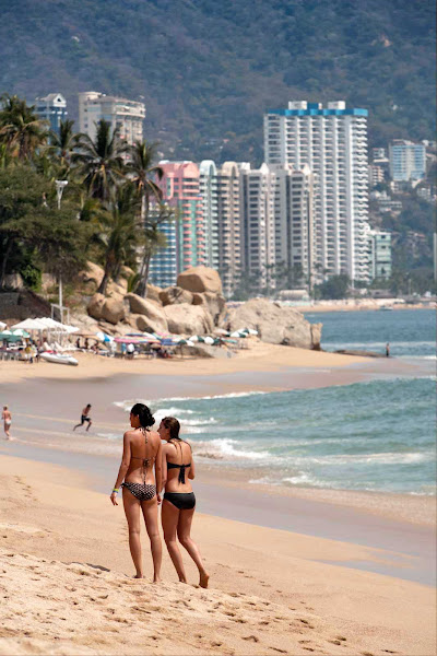 Two women walk on Acapulco's world-famous beach.