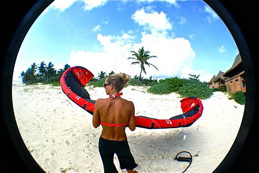 Morph-Kiteboarding-fish-eye - A kiteboarder waits for her turn on the beach in Mexico.