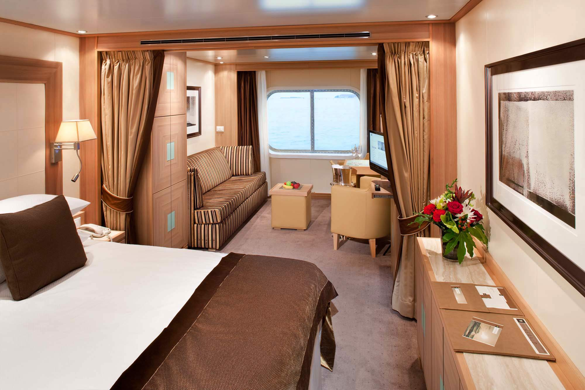 The Ocean View Suites on Seabourn Odyssey, Sojourn, and Quest feature a spacious living room with dinning area for two, your choice of beds, a fully stocked bar and refriderator, and an interactive media center.